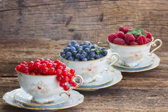 Red currant, raspberry and blueberry in cups. On wood Stock Photos