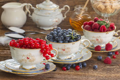 Red currant, raspberry and blueberry in cups. On wooden table Stock Photography