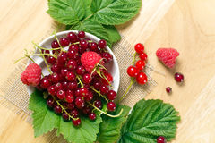 Red currant and raspberry on the glass bowl. Red currant and raspberry with leaves on the glass bowl Stock Photos