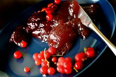 Closeup of red currant marmalade served on dark blue plate. Dark food photo. Red currant, redcurrant, jelly or marmalade served on tilted dark blue plate, with stock image