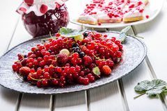 Red currant sponge cake. Plate with Assorted summer berries, raspberries, strawberries, cherries, currants, gooseberries. Fresh summer garden fruit Stock Image