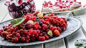 Red currant sponge cake. Plate with Assorted summer berries, raspberries, strawberries, cherries, currants, gooseberries. Fresh summer garden fruit Royalty Free Stock Photo