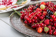 Red currant sponge cake. Plate with Assorted summer berries, raspberries, strawberries, cherries, currants, gooseberries. Royalty Free Stock Image