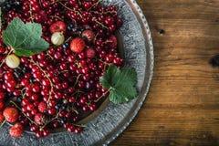 Red currant sponge cake. Plate with Assorted summer berries, raspberries, strawberries, cherries, currants, gooseberries. Fresh summer garden fruit Stock Images
