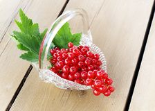 Red currants. Basket of red currants on a wood background Royalty Free Stock Photos