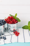 Red currants and blueberries in small metal buckets Stock Photography