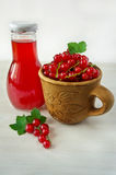Red currants in a clay cup and a bottle of juice Stock Images