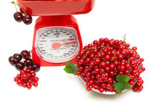 Red currants and kitchen scales on a white background Royalty Free Stock Photography
