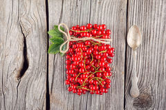 Red currants like vial with twine and metal spoon and jam on wooden background, creative idea for healthy lifestyle, raw food Stock Photo