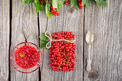 Red currants like vial with twine, metal spoon and jam on wooden background, creative idea for healthy lifestyle, raw food Royalty Free Stock Photo