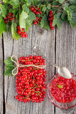 Red currants like vial with twine, metal spoon and jam on wooden background, creative idea for healthy lifestyle, raw food Royalty Free Stock Photography