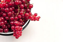 Red currants on white background. A bowl of red currants on a light wooden table Stock Photo