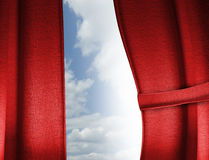 Red curtain. S with one side drawn back to expose a brightness with a cloudy sky Royalty Free Stock Image
