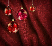 Red curtain christmas balls. Christmas balls hanging against vivid red folded damask curtain royalty free stock image