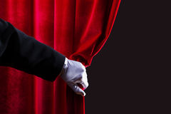 Red curtain. Close up of hand in white glove open the curtain. Place for text Royalty Free Stock Photography