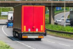 Red curtain side lorry truck on uk motorway in fast motion stock photos