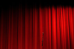 Red Curtain on Stage With Microphone. A red curtain in shadow on stage with a silver microphone on a stand Royalty Free Stock Photography