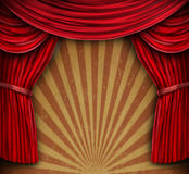 Red Curtains On An Old Grunge Wall. Red velvet curtains or drapes on an old grunge wall with a radial sun burst design as an entertainment background for Royalty Free Stock Photo