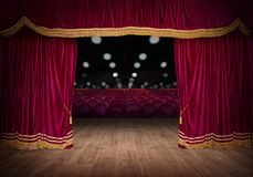 The red curtains are opening for the theater show. The red curtains of the stage are opening for the theater show stock photography