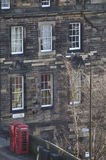 Two red telephone boxes with house. The red curtains in the window are fitting best to the red telephone box next to a beautiful house in Edinburgh royalty free stock image