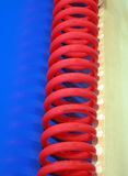 Red curved cable, blue surface, Royalty Free Stock Photos