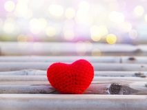 Red cushion heart shape on bamboo wood stock photo
