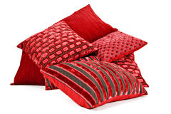 Red cushions stacked up on a white background. With space for text stock images