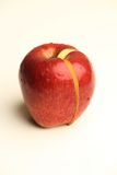 A red cut apple. An isolated apple with a cut piece Stock Image