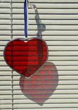 Red Cut Glass Heart Reflection in a Window with Blinds Royalty Free Stock Images
