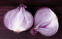Red cut half onion close up photo. On wooden board Royalty Free Stock Image