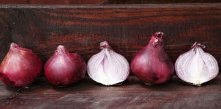 Red cut half onion close up photo. On wooden board Royalty Free Stock Images