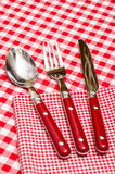 Red cutlery on a napkin in a restaurant Stock Photo