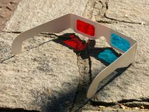 Red cyan stereophotography anaglyph 3D glasses on rocks ground pattern. Red cyan stereophotography anaglyph 3D glasses on ground rocks pattern stock photography