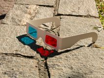 Red cyan stereophotography anaglyph 3D glasses on rocks ground pattern. Red cyan stereophotography anaglyph 3D glasses on ground rocks pattern royalty free stock images
