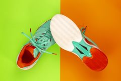 Tennis shoes in studio. Red, cyan, white pair of new tennis shoes in studio shot over green, orange background. Directly from above royalty free stock photos