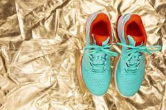 Tennis shoes in studio. Red, cyan, white pair of new tennis shoes in studio shot over reflective golden background. Directly from above stock photography
