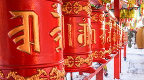 Red cylinders with Buddhist mantras and color flags. Buddhist Temple Datsan Gunzechoinei in Sankt-Peterburg. Russia. Royalty Free Stock Photography