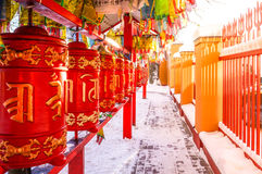 Red cylinders with Buddhist mantras and color flags. Buddhist Temple Datsan Gunzechoinei in Sankt-Peterburg. Russia. Stock Photos