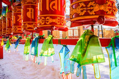 Red cylinders with Buddhist mantras and color flags. Buddhist Temple Datsan Gunzechoinei in Sankt-Peterburg. Russia. Stock Photo