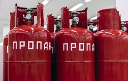 Red cylinders of propane gas. The inscription in Russian - propane stock photos