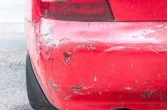 Red damaged car in crash accident with scratched paint and dented rear bumper metal body.  Royalty Free Stock Photo