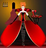 Red dame. On the stairs, lighted by candles, is spectacular red-haired woman in red magnificent dress, behind the table where the hat and fan Stock Images