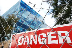 Red danger sign. Behind a metal fence Royalty Free Stock Image