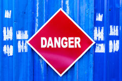 A red Danger sign mounted to a blue metal wall. Stock Photography