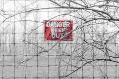 Red Danger sign posted to barbed fence tangled in branches, warn Stock Photography