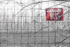Red Danger sign posted to barbed fence tangled in branches, warn Royalty Free Stock Photo