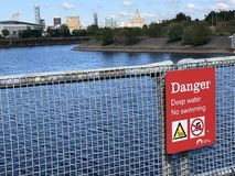 A red danger sign. A sign warns people against swimming due to deep water, mounted on metal railings, Birkenhead Docks, Wirral Stock Photo