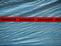 Red Danger Tape Over a Blue Wall Background Stock Photo
