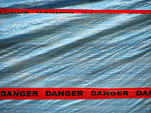 Red Danger Tape Over a Blue Wall Background Royalty Free Stock Images