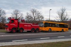 Red Danish Falck Wrecker truck pulling a broken down bus Royalty Free Stock Photo